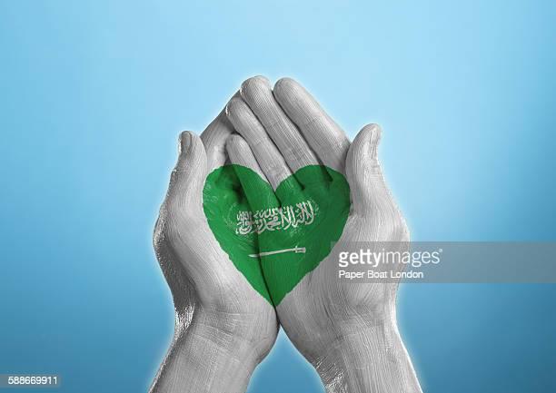 saudi arabia heart shaped flag painted on a hand - saudi arabian flag stock photos and pictures