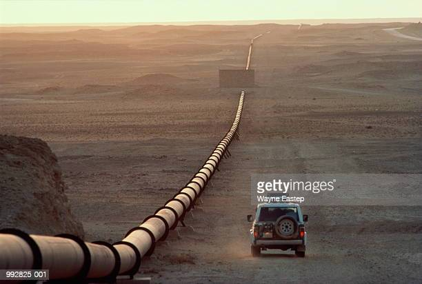 saudi arabia, main oil pipeline, car driving by at dusk - gulf countries stock pictures, royalty-free photos & images