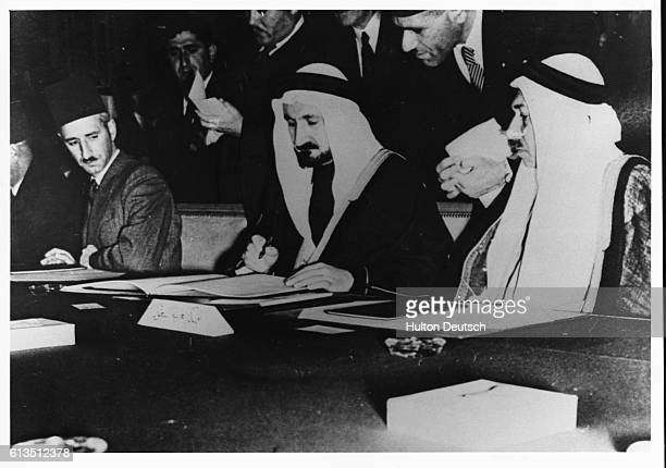 Saudi Arabian delegates acting Minister for Foreign Affairs Sheikh Youssek Yassin and El Zerekly sign the League of Arab States charter in Cairo...