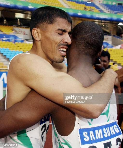Saudi Arabian Jamal Al Saffar hugs his compatriot Salem Al Yami after winning the men's 100m final during the 14th Asian Games in Busan 08 October...