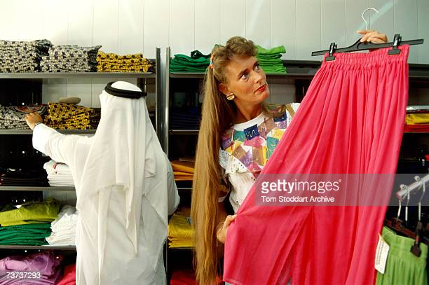 A Saudi Arabian man shops in United Colours of Benetton in Dhahran alongside a longhaired western woman December 1990