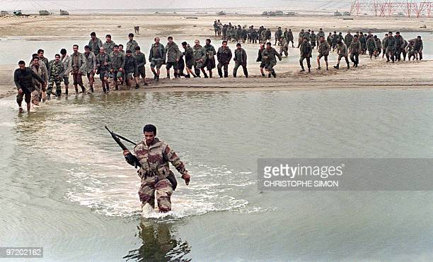 A Saudi Arabian soldier leads Iraqi prisoners through a pool of water in the Kuwaiti desert 25 February 1991 as allied forces continue to advance on...