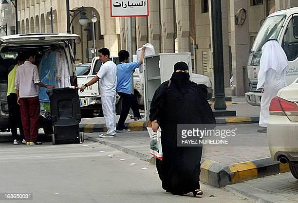 A Saudi Arabian woman walks past a local hospital in the center of the Saudi capital Riyadh on May 13 2013 Fifteen people in Saudi Arabia have died...