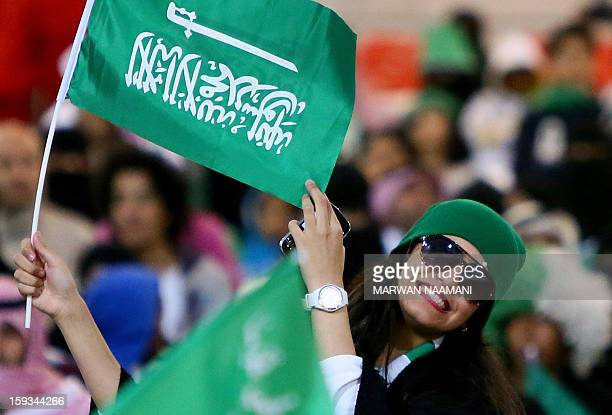 A Saudi Arabian woman waves her country's flag prior the start of Saudi Arabia's match against Kuwait in the 21st Gulf Cup in Manama on January 12...
