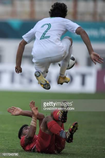 Saudi Arabia's Abdullah Hassun Tarmin jumps over an Iran player during the men's football Group F match between Iran and Saudi Arabia at the 2018...