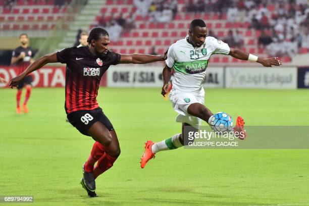 Saudi Arabia's AlAhli club defender Motaz Hawsawi vies for the ball against UAE AlAhli club forward Makhete Diop during the AFC Champions League...