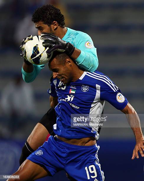 Saudi Arabia's alAhli club goalkeeper Abdullah alMuaiouf gathers the ball ahead of Dubai's alNasr club player Bruno Cesar Correa during their AFC...
