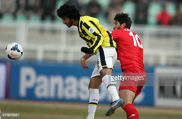 Saudi Arabia's AlIttihad player Basem Mohsen alMontashri tries to stop Tractor Sazi Tabriz's Karim Ansarifard from heading the ball during their AFC...