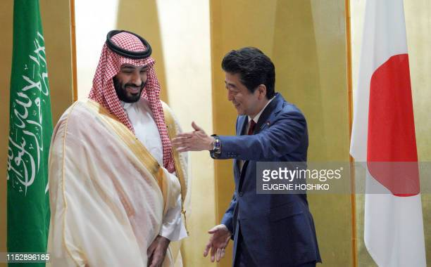 Saudi Arabia's Crown Prince Mohammed bin Salman is escorted by Japanese Prime Minister Shinzo Abe during their meeting in Osaka on June 30 2019