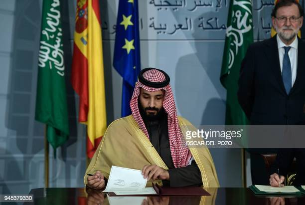 Saudi Arabia's crown prince Mohammed bin Salman signs agreements as Spanish Pime Minister Mariano Rajoy looks on at La Moncloa palace in Madrid on...