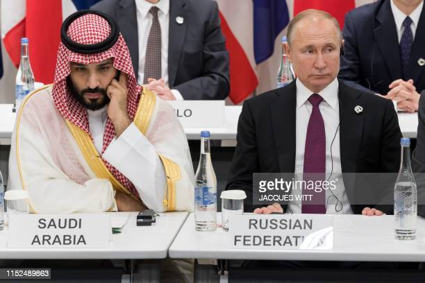 Saudi Arabia's Crown Prince Mohammed bin Salman sits beside Russia's President Vladimir Putin as they attend a meeting on the digital economy at the...