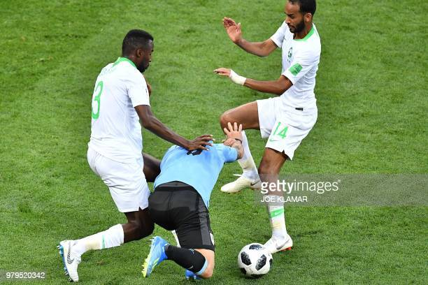 TOPSHOT Saudi Arabia's defender Osama Hawsawi and Saudi Arabia's midfielder Abdullah Otayf fights for the ball with Uruguay's forward Luis Suarez...