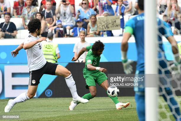 Saudi Arabia's defender Yasser AlShahrani attempts a shot on goal as Egypt's defender Ahmed Hegazi and goalkeeper Essam El Hadary look on during the...