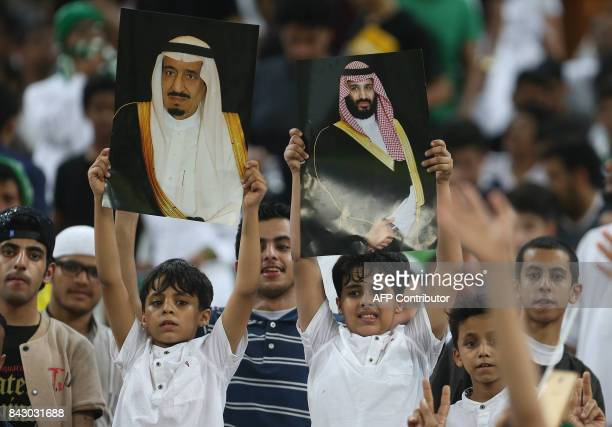 Saudi Arabia's fans hold up portraits of Saudi King Salman and Crown Prince Mohammed bin Salman during the FIFA World Cup 2018 qualification football...