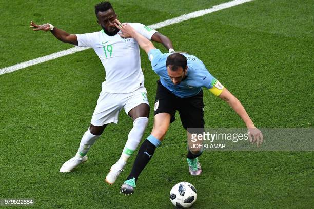 TOPSHOT Saudi Arabia's forward Fahad AlMuwallad fights for the ball with Uruguay's defender Diego Godin during the Russia 2018 World Cup Group A...