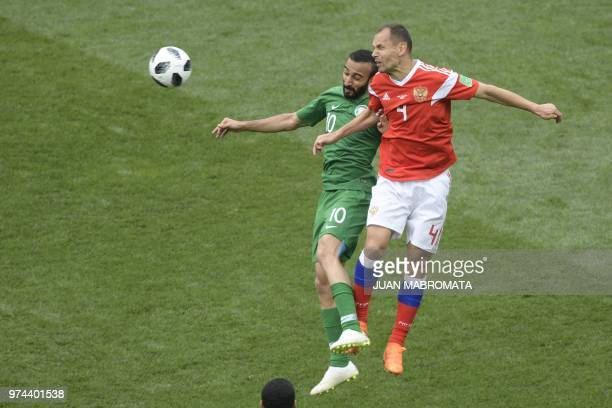 Saudi Arabia's forward Mohammed AlSahlawi and Russia's defender Sergey Ignashevich compete for the ball during the Russia 2018 World Cup Group A...