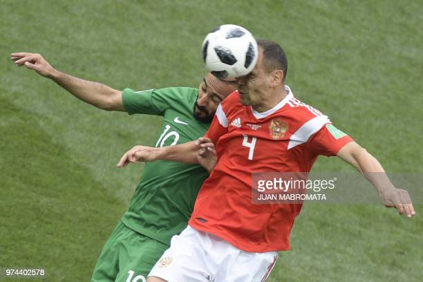 TOPSHOT Saudi Arabia's forward Mohammed AlSahlawi and Russia's defender Sergey Ignashevich compete for the ball during the Russia 2018 World Cup...