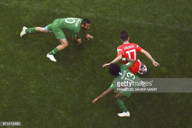 Saudi Arabia's forward Mohammed AlSahlawi Russia's midfielder Aleksandr Golovin and Saudi Arabia's defender Yasser AlShahrani compete for the ball...