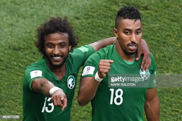 Saudi Arabia's forward Salem AlDawsari celebrates with teammate Saudi Arabia's defender Yasser AlShahrani after scoring his team's winning goal...