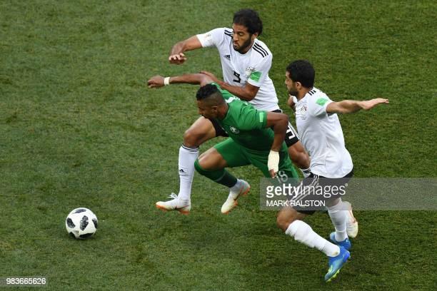 Saudi Arabia's forward Salem AlDawsari dribbles past Egypt's defenders during the Russia 2018 World Cup Group A football match between Saudi Arabia...
