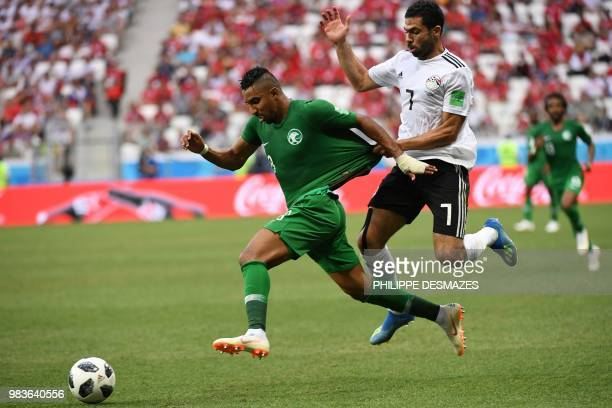 TOPSHOT Saudi Arabia's forward Salem AlDawsari is held back by Egypt's defender Ahmed Fathi during the Russia 2018 World Cup Group A football match...