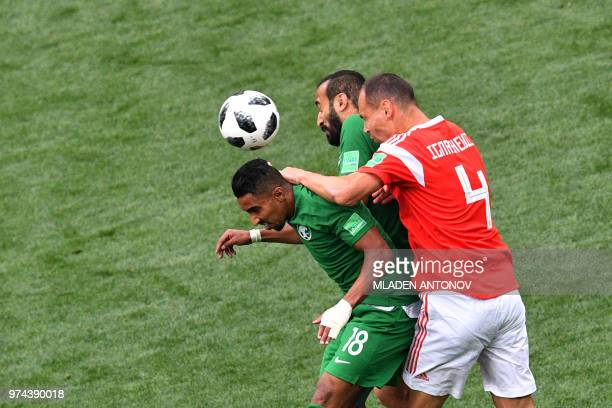 Saudi Arabia's forward Salem AlDawsari Saudi Arabia's forward Mohammed AlSahlawi and Russia's defender Sergey Ignashevich compete for the ball during...