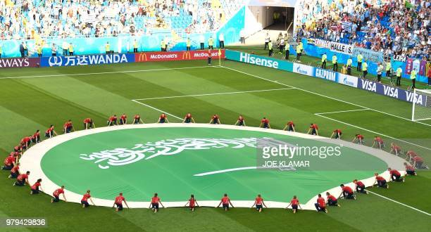 Saudi Arabia's giant flag is seen on the pitch before the start of the Russia 2018 World Cup Group A football match between Uruguay and Saudi Arabia...