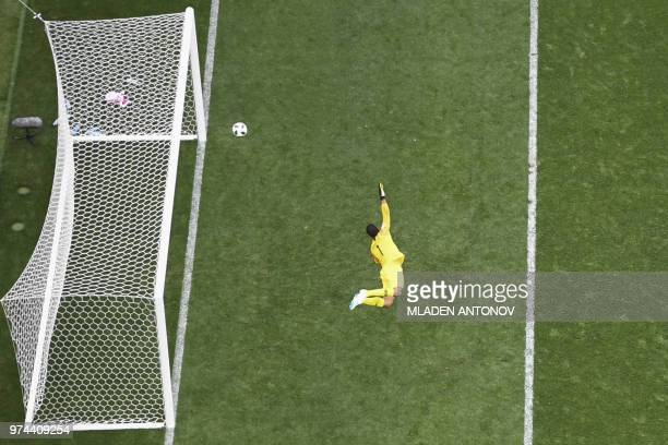 TOPSHOT Saudi Arabia's goalkeeper Abdullah AlMayouf dives as Russia's score their fourth goal during the Russia 2018 World Cup Group A football match...