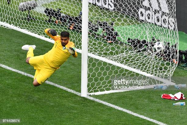 Saudi Arabia's goalkeeper Abdullah AlMayouf fails to stop a goal during the Russia 2018 World Cup Group A football match between Russia and Saudi...