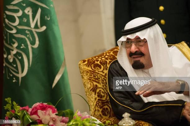 Saudi Arabia's King Abdullah bin Abdulaziz alSaud talks with French President Francois Hollande during their meeting at the Saudi Royal palace in...