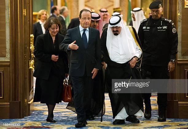 Saudi Arabia's King Abdullah bin Abdulaziz alSaud walks with French President Francois Hollande after their meeting at the Saudi Royal palace in...