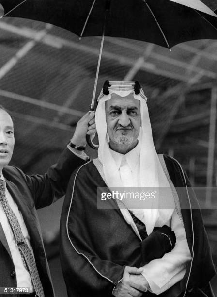 Saudi Arabia's King Faisal bin Abdul Aziz al Saud brother of former King Saud stands under umbrella in May 1971 during his visit to Japan Following...