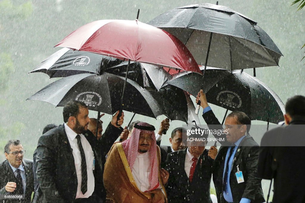 TOPSHOT - Saudi Arabia's King Salman bin Abdul Aziz (centre L) and Indonesia's President Joko Widodo (centre R) walk in heavy rain at the presidential palace in Bogor, West Java on March 1, 2017. Cheering crowds welcomed King Salman on March 1 as he began the first visit by a Saudi monarch to Indonesia for almost 50 years, seeking stronger economic ties with the world's most populous Muslim-majority country. / AFP PHOTO / POOL / Achmad Ibrahim