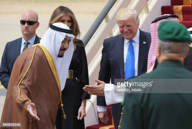 Saudi Arabia's King Salman bin Abdulaziz alSaud shows the way to US President Donald Trump and First Lady Melania Trump upon arrival at King Khalid...