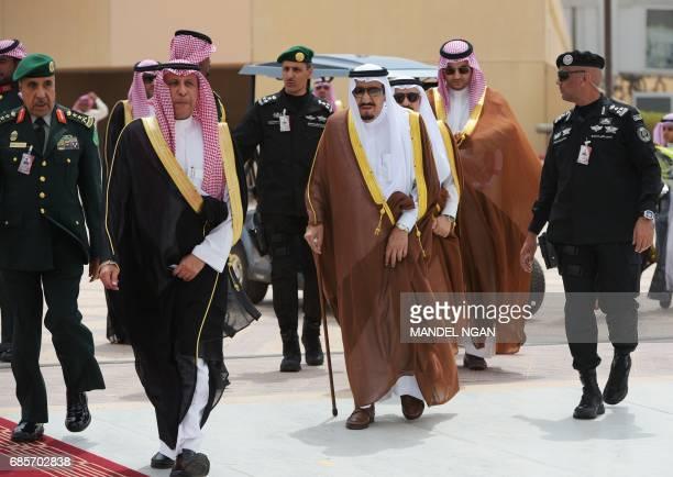 Saudi Arabia's King Salman bin Abdulaziz alSaud walks across the tarmac to greet US President Donald Trump at King Khalid International Airport in...