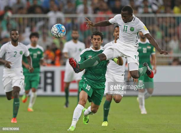 Saudi Arabia's midfielder Abdulmalek alKhaibri jumps for the ball as Iraq's forward Alaa alAzzawi defends during the Asian Cup qualifying football...