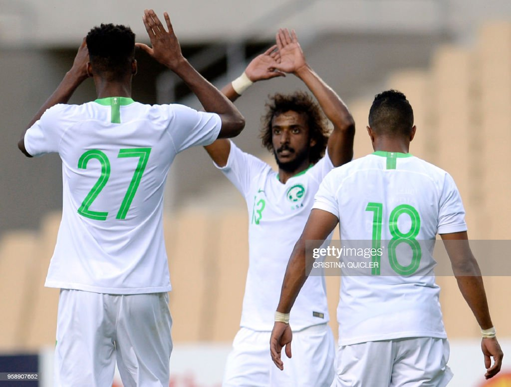 Saudi Arabia's midfielder Mohamed Kanno (L) celebrates a goal with Saudi Arabia's defender Yasser Al-Shahrani (C) during the friendly football match between Saudi Arabia and Greece at the Olympic stadium in Sevilla on May 15, 2018.
