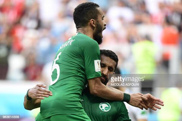 TOPSHOT Saudi Arabia's midfielder Salman AlFaraj is congratulated by defender Mohammed AlBurayk after scoring from the penalty spot during the Russia...