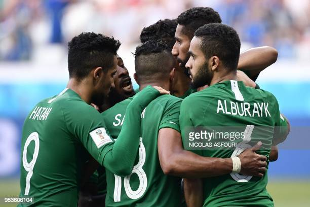Saudi Arabia's midfielder Salman AlFaraj is congratulated by teammates after scoring from the penalty spot during the Russia 2018 World Cup Group A...