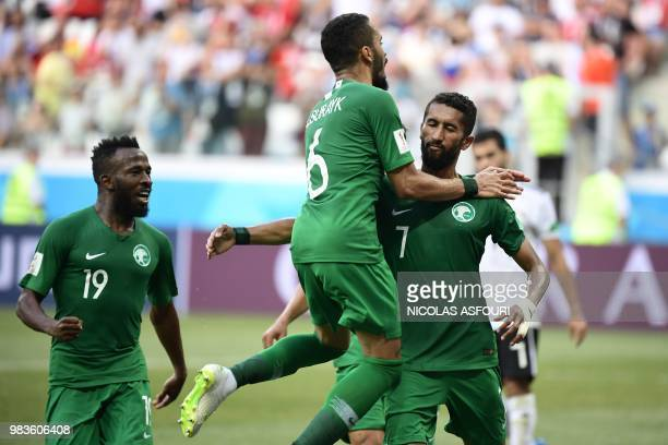 Saudi Arabia's midfielder Salman AlFaraj is congratulated by teammates after scoring after scoring from the penalty spot during the Russia 2018 World...