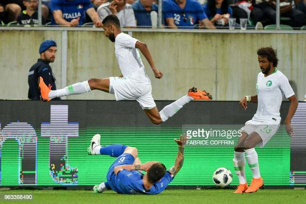 Saudi Arabia's midfielder Salman AlFaraj jumps over Italy's defender Alessio Romagnoli during the friendly football match between Italy and Saudi...
