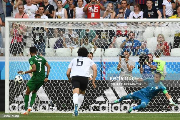 TOPSHOT Saudi Arabia's midfielder Salman AlFaraj scores from the penalty spot past Egypt's goalkeeper Essam El Hadary as Egypt's defender Ahmed...