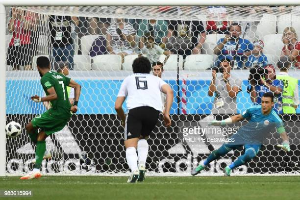 Saudi Arabia's midfielder Salman AlFaraj scores from the penalty spot past Egypt's goalkeeper Essam El Hadary as Egypt's defender Ahmed Hegazi...