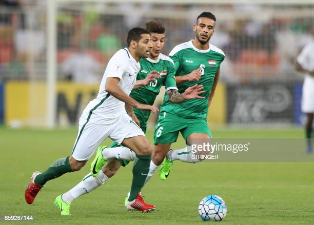 Saudi Arabia's midfielder Taiseer alJassam dribbles the ball as Iraq's defender Dhurgham Ismael and Ali Adnan Kadhim run back to defend during the...