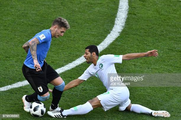 TOPSHOT Saudi Arabia's midfielder Taisir AlJassim injures himself as fighting for the ball with during the Russia 2018 World Cup Group A football...