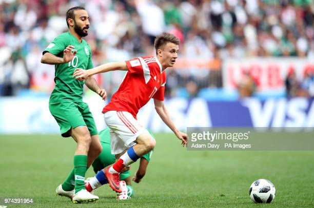 Saudi Arabia's Mohammad AlSahlawi and Russia's Aleksandr Golovin battle for the ball during the FIFA World Cup 2018 Group A match at the Luzhniki...