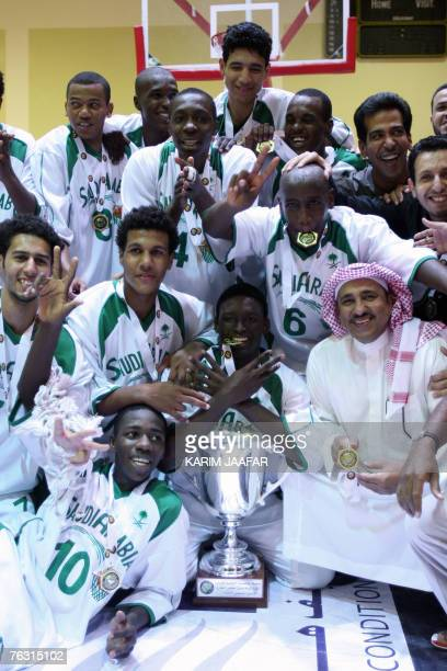 Saudi Arabia's national basketball team player and staff pose for a picture after winning the final match against the United Arab Emirates for the...