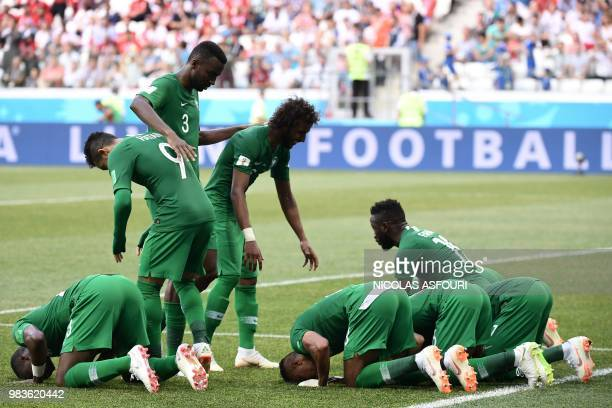 Saudi Arabia's players react after midfielder Salman AlFaraj scored from the penalty spot during the Russia 2018 World Cup Group A football match...