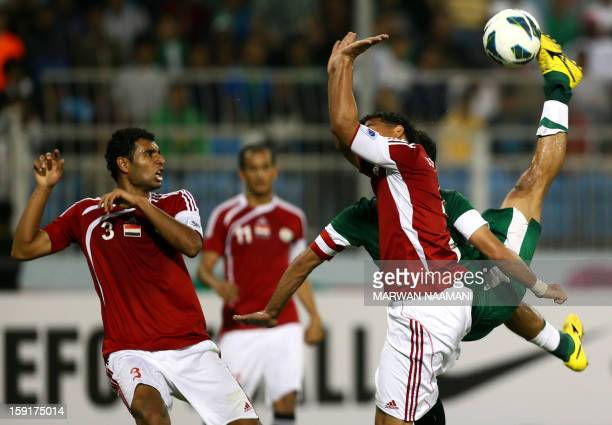 Saudi Arabia's Yasser alQahtani kicks the ball past Yemen's Mohammed Fouad Omar and Ahmed Sadeq Abdulwahab during their 21st Gulf Cup football match...