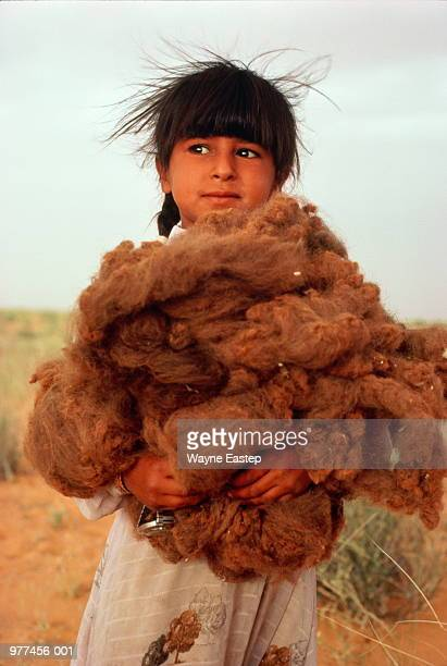 Saudi Arabia,young girl holding large pile of wool in arms outdoors